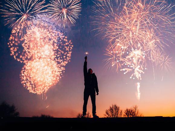 Man standing under fireworks